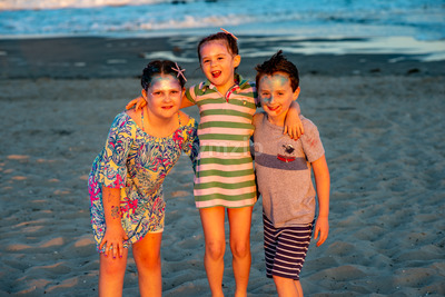 Brother and sisters on beach at sunset during the golden hour Stock Photo