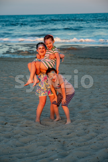 View of Brother and sisters on beach at sunset during the golden hour