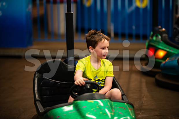 Happy young boy rides electric bumper car amusement ride on shore boardwalk Stock Photo