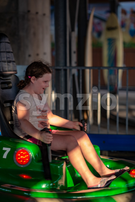 View of Happy young girl rides electric bumper car amusement ride on shore boardwalk