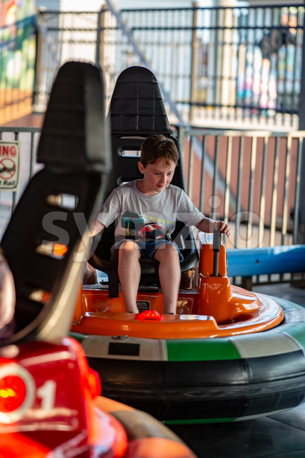 View of Happy young boy rides electric bumper car amusement ride on shore boardwalk