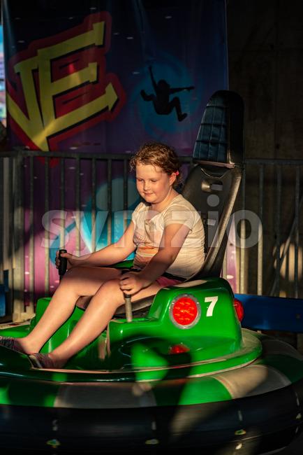 Happy young girl rides electric bumper car amusement ride on shore boardwalk Stock Photo
