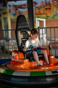 Happy young boy rides electric bumper car amusement ride on shore boardwalk Stock Photo