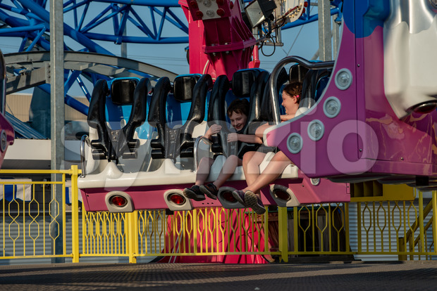 View of Happy young brother and sister having fun on boardwalk amusement ride