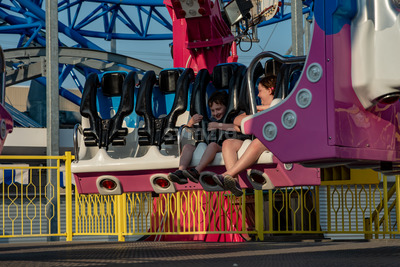 Happy young brother and sister having fun on boardwalk amusement ride Stock Photo