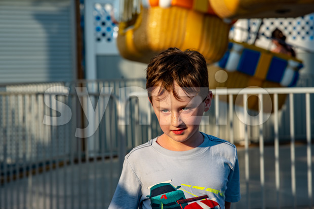 Happy young boy having fun on boardwalk amusement ride Stock Photo