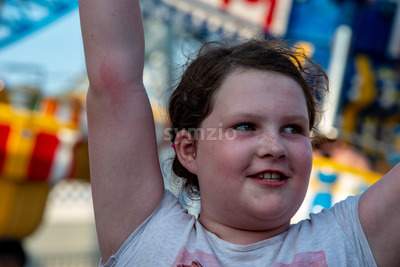 Happy young girl having fun on boardwalk amusement ride Stock Photo
