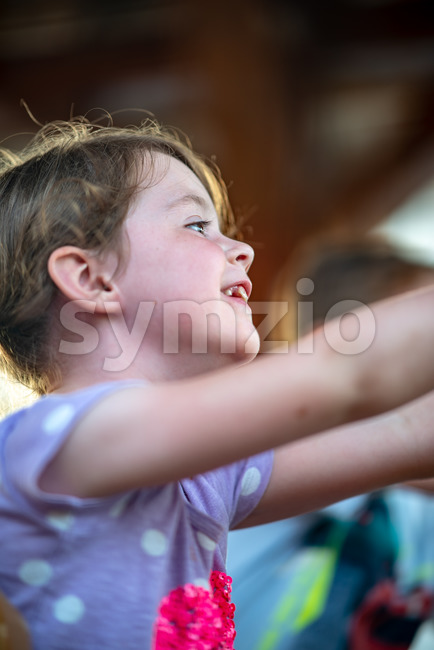 View of Happy young girl having fun on boardwalk amusement ride