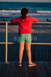 Young cute little girl on the boardwalk with back to camera looking towards the ocean surf Stock Photo