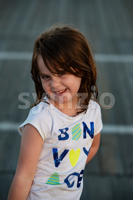 View of Young cute little girl on the boardwalk looking at camera smiling