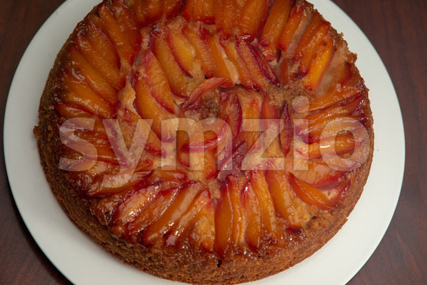 View of cake with nectarines on white plate on top of dining table