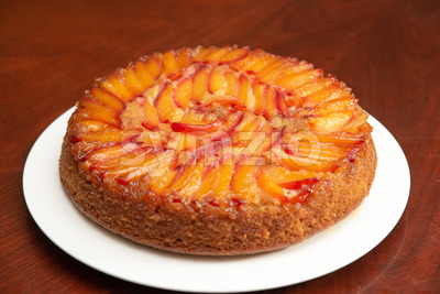Cake with nectarines on white plate on top of dining table Stock Photo