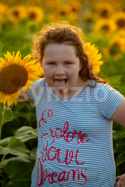View of Beauty joyful young girl with sunflower enjoying nature and laughing on summer sunflower field. Sunflare, sunbeams, glow sun. ...